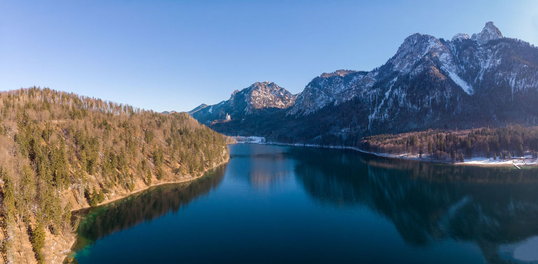 Scenic view of lake alpsee and mountains against clear blue sky