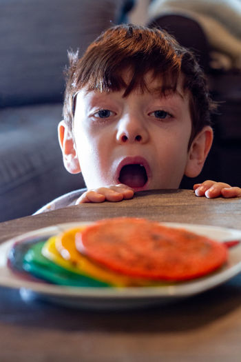 A cute blue-eyed boy looking at a plate of colorful pancakes with his mouth open