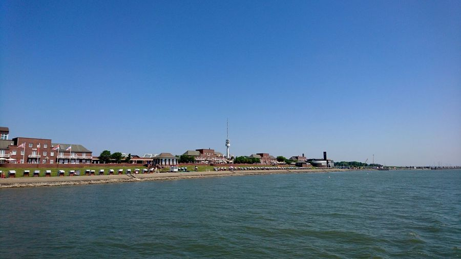 Off the coast of Wilhelmshaven. Wilhelmshaven Germany Lower Saxony Niedersachsen Nordsee North Sea Coast Shore Waterfront Water From A Boat Blue Blue Sky Summer Cityscape Clear Sky Water Sea Beach Blue Façade Sunny Sand Tourist Resort