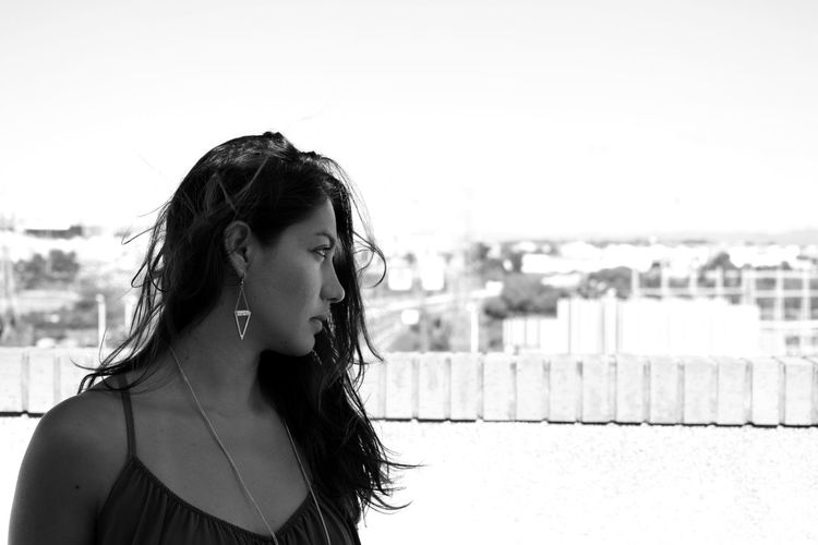 Woman looking away against clear sky