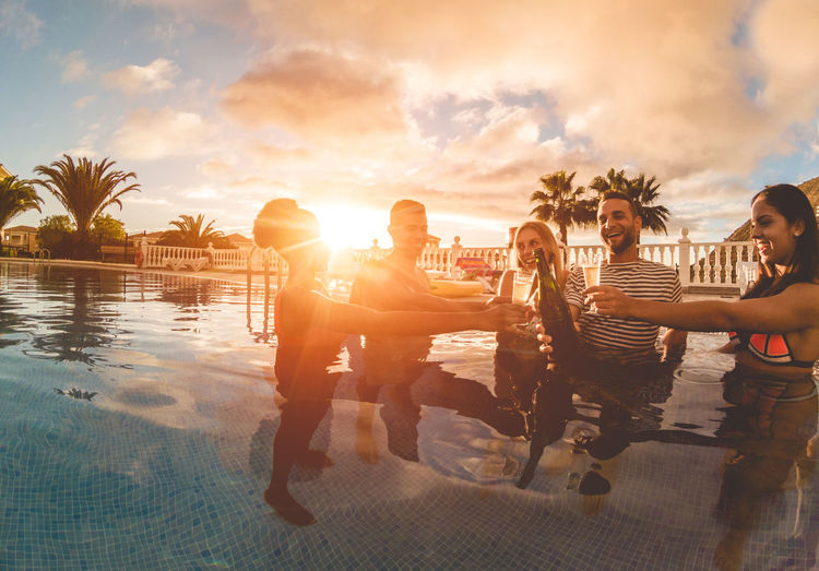 Friends Toasting Beer Bottles And Glasses In Swimming Pool Against Sky During Sunset