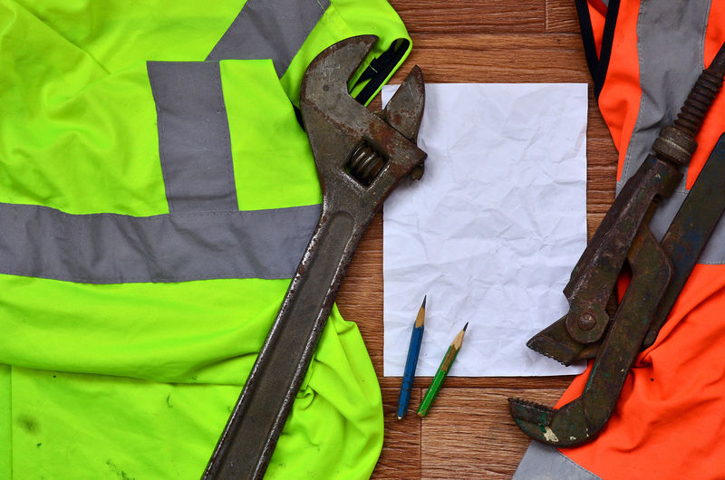 Close-up of work tools and paper on reflective clothes