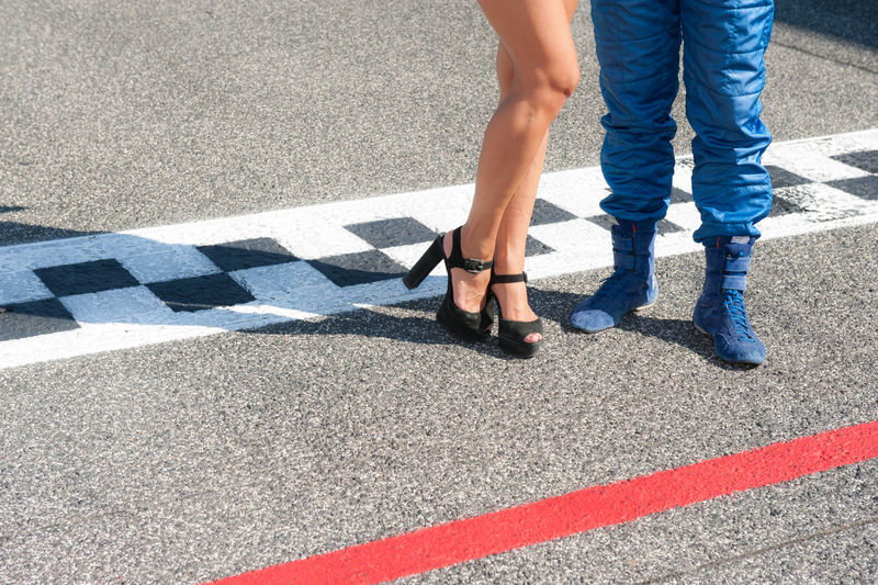 Low section of grid-girl and driver standing on finish line