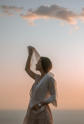 Woman holding fabric while standing against sky during sunset