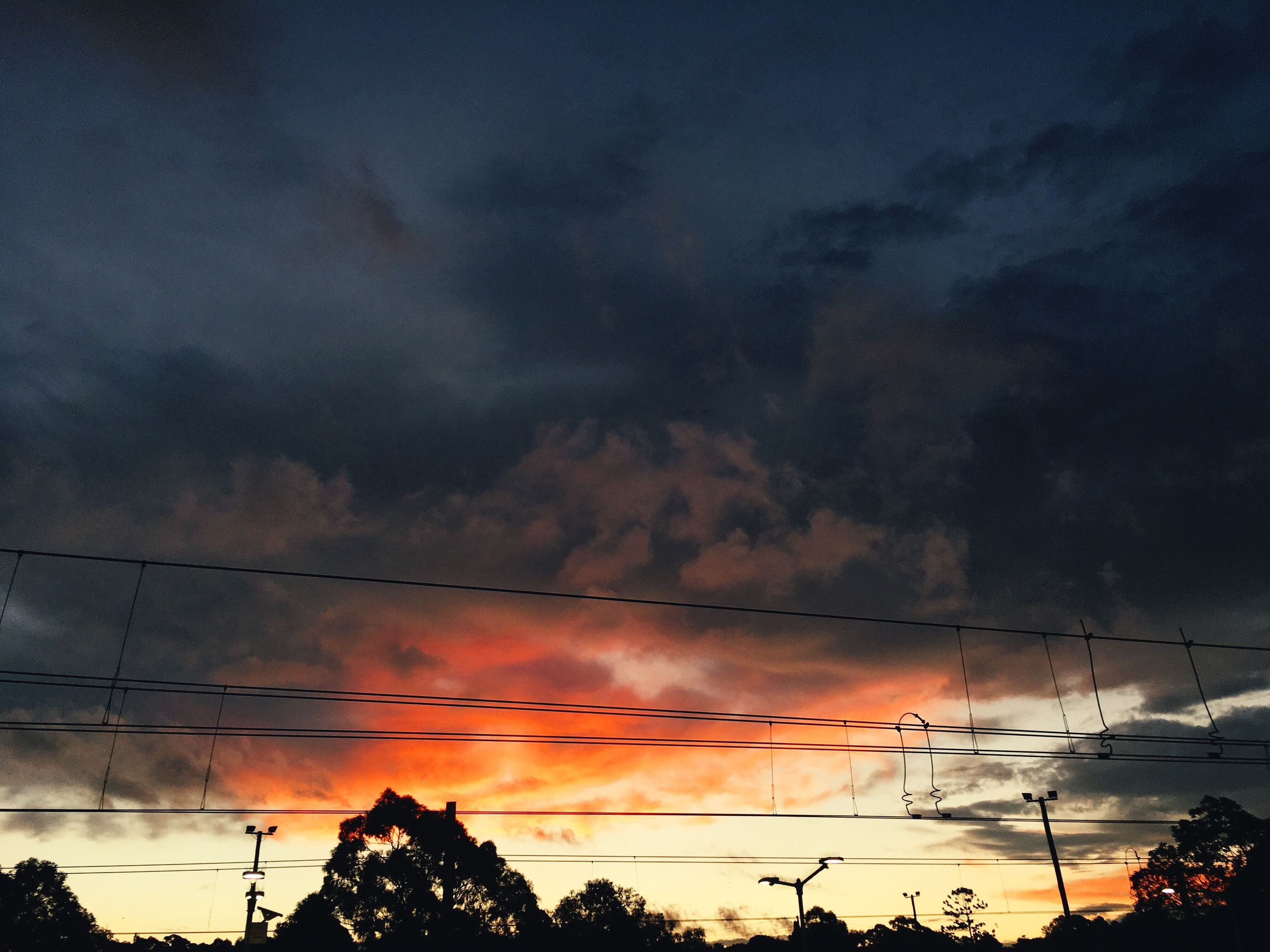 low angle view, sky, cloud - sky, power line, silhouette, cloudy, sunset, electricity pylon, tree, electricity, power supply, beauty in nature, scenics, weather, tranquility, cable, nature, cloud, dramatic sky, connection