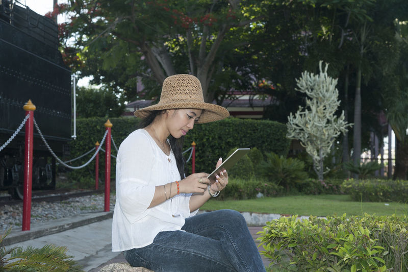 Woman using digital tablet while sitting at park