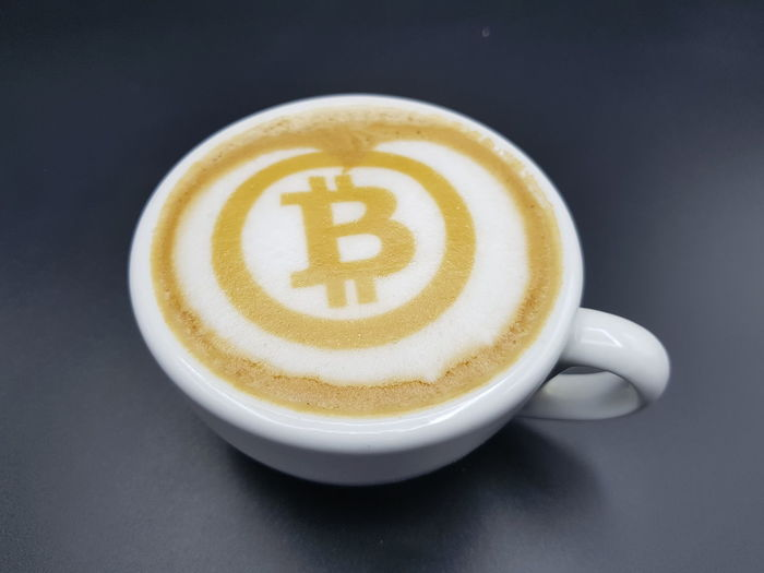 Close-up of bitcoin sign in cappuccino on gray background