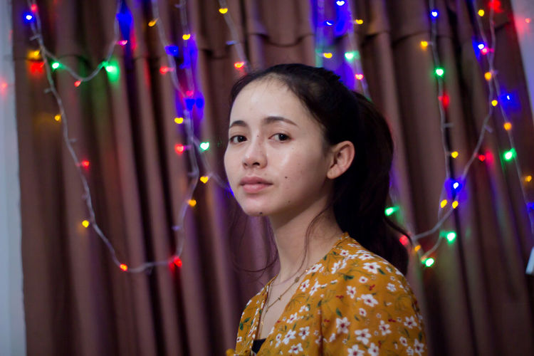 Portrait of woman against illuminated lights