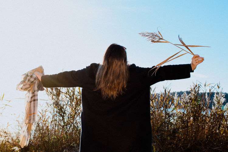 Rear view of woman with arms outstretched standing against plants