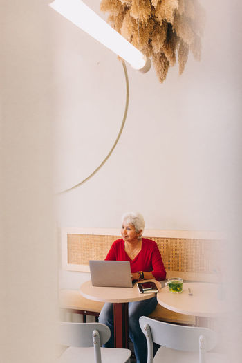 Woman using phone while sitting on chair
