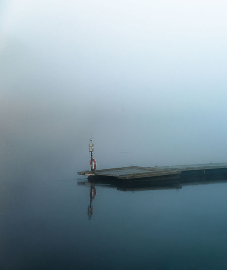 Pier over calm lake during foggy weather