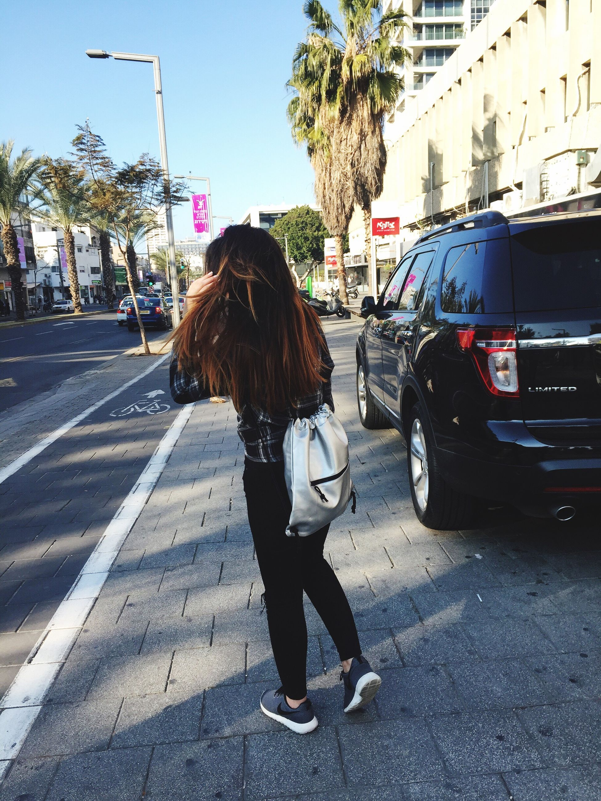 real people, full length, rear view, one person, street, transportation, lifestyles, outdoors, day, mode of transport, land vehicle, car, women, leisure activity, city, one woman only, sky, architecture, only women, adults only, people, adult
