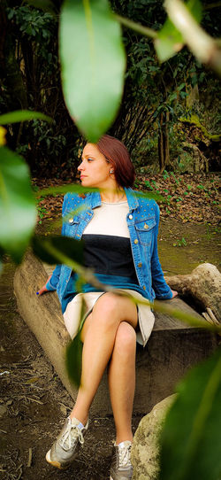 Full length of woman sitting on on wood in forest