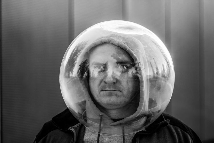 Man wearing spherical shape glass against wall