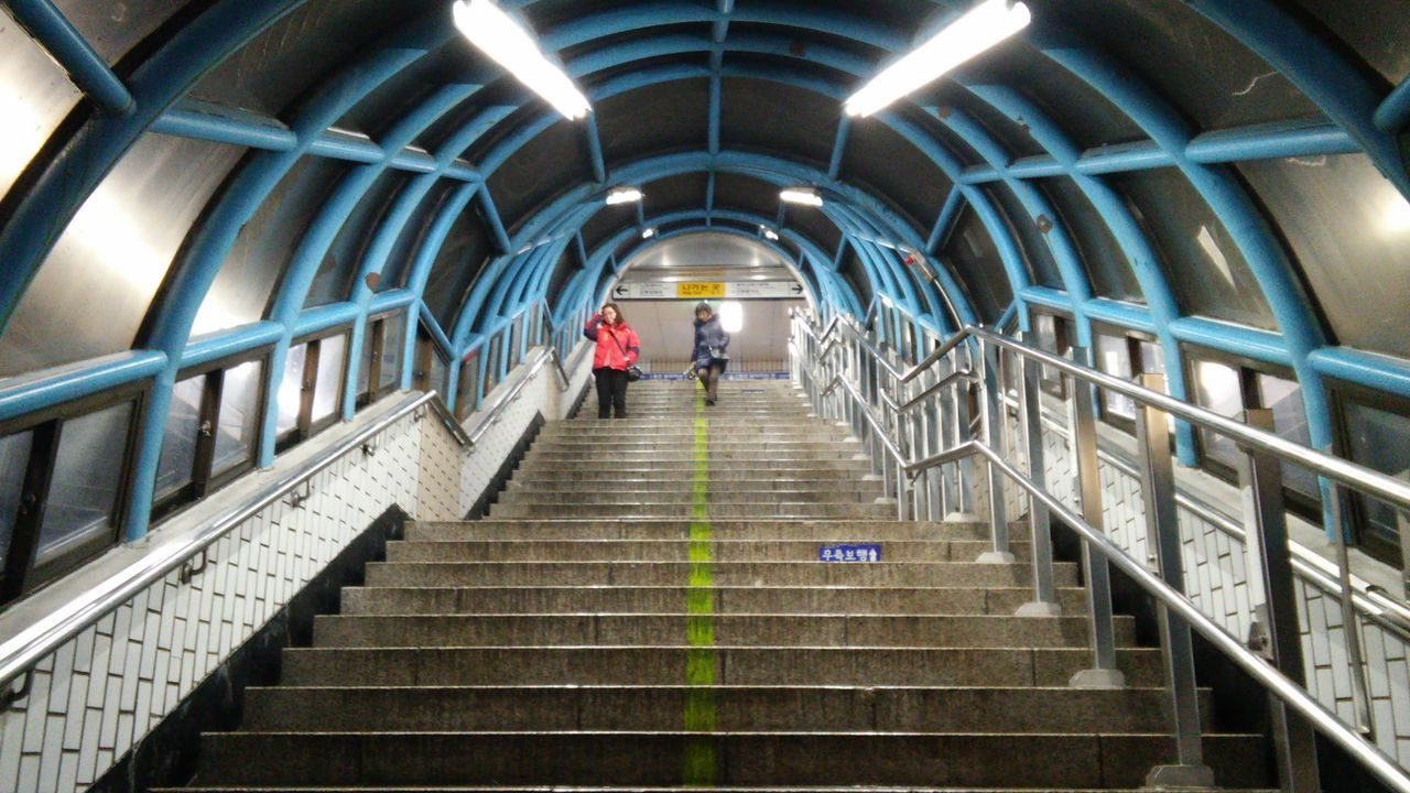 steps, steps and staircases, staircase, full length, real people, one person, illuminated, railing, built structure, tunnel, architecture, subway station, indoors, men, low angle view, the way forward, lifestyles, women, modern, day, adult, people, adults only
