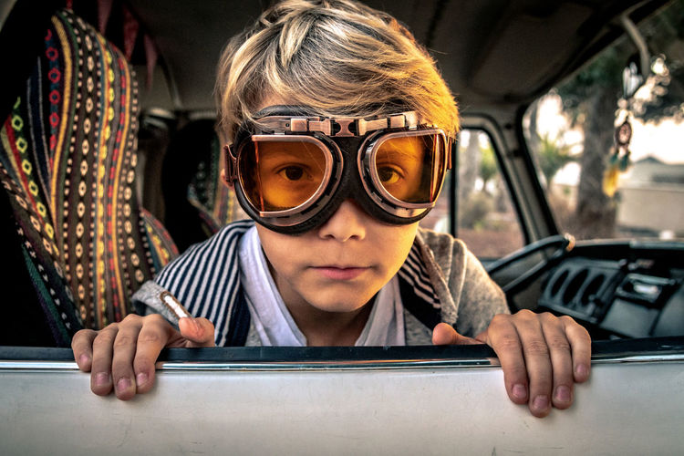 Portrait Of Boy Wearing Protective Eyewear While Sitting In Travel Trailer