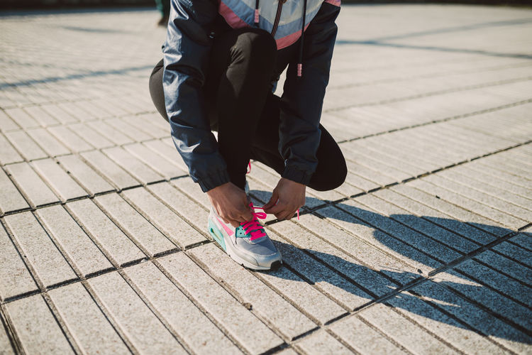 Low Section Of Female Athlete Tying Shoelace At Footpath