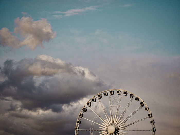 Ferris wheel against raining clouds