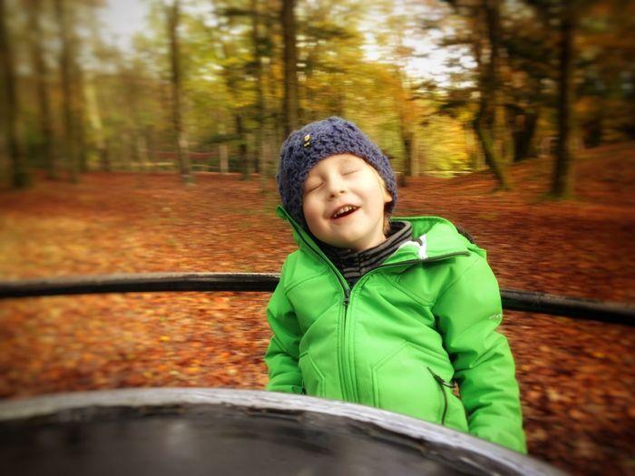 Boy enjoying on merry-go-round in park
