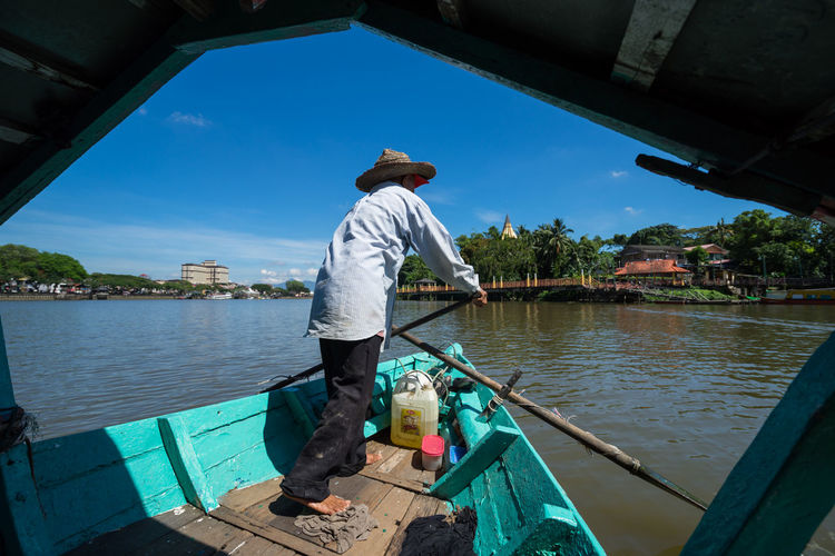 Rear view of man boating in sarawak river against sky