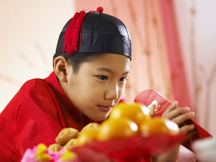 Close-up of teenage boy in traditional clothes looking in envelope