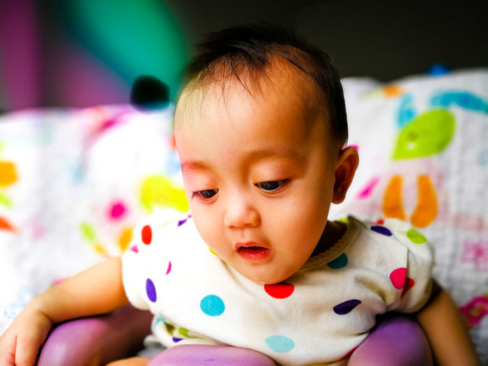 Close-up of cute baby girl drooling while sitting on chair at home