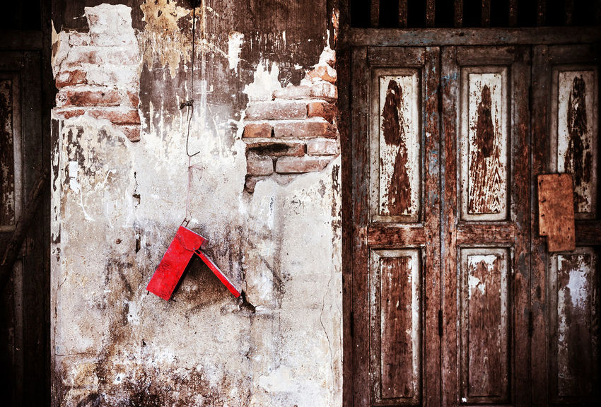An old backdoor on dilapidated grungy brick wall with red old shabby mailbox. Abandoned Buildings Brick Wall Close-up Damaged Wall Decay Dilapidated Building Door Grungy Concrete Wall Grungy Textures Mailbox Malfunctioning No People Nutcrackers Old Buildings Red Color Shabby Wooden