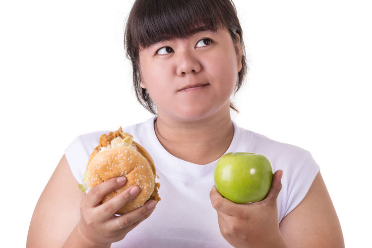 Portrait of smiling woman holding apple against white background