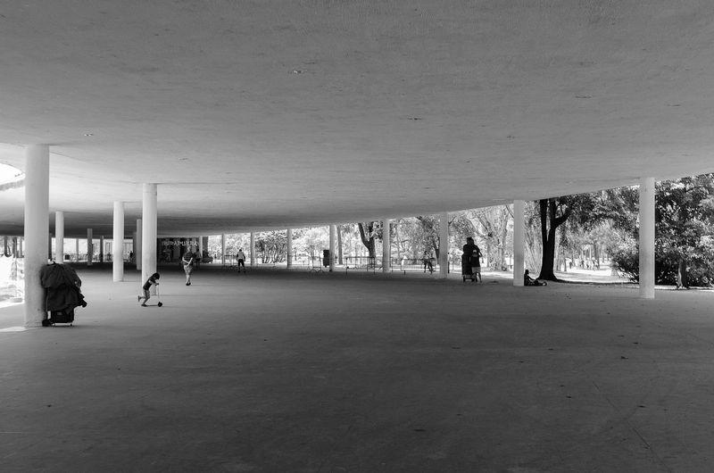 People walking on empty floor against building