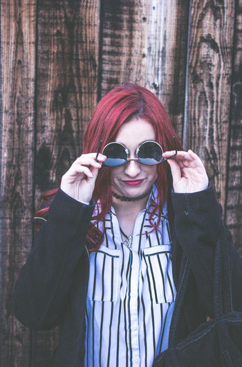 Woman holding sunglasses on face while standing against wooden wall