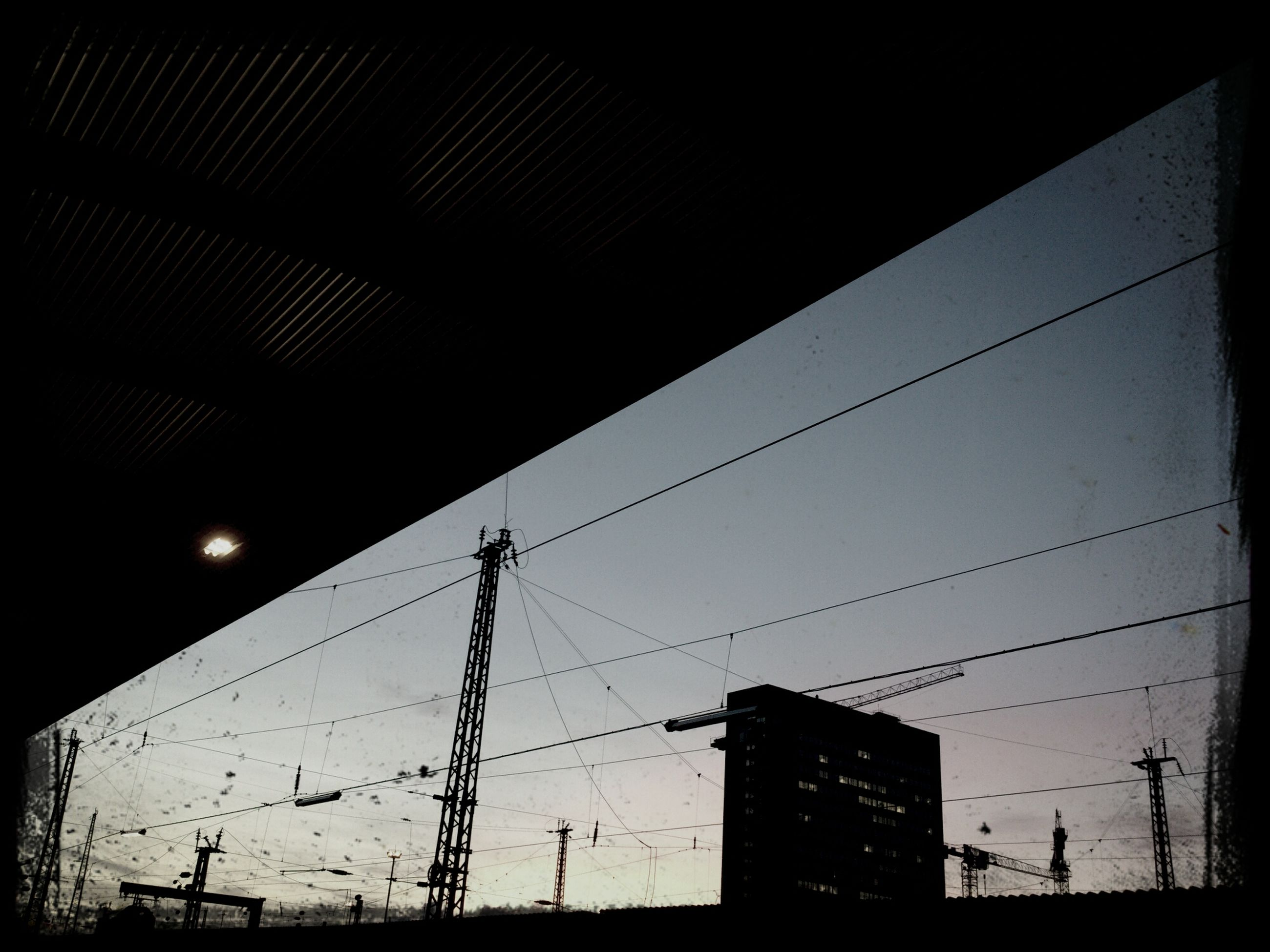power line, low angle view, electricity pylon, electricity, power supply, cable, connection, fuel and power generation, silhouette, built structure, architecture, sky, technology, building exterior, power cable, dusk, no people, outdoors, complexity, sunset