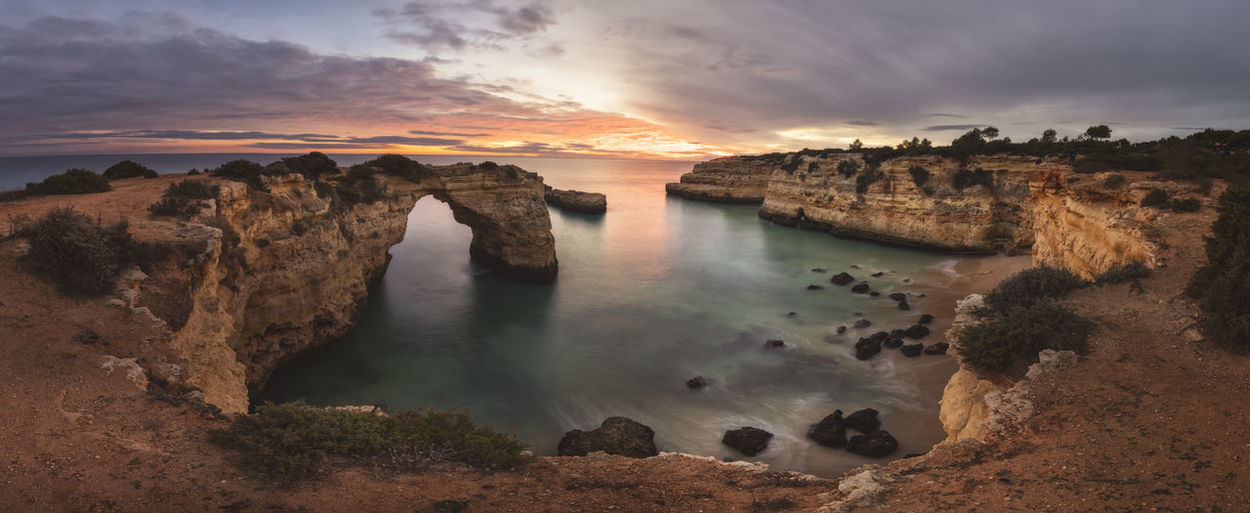 Panoramic view of rocks on sea against sky during sunset