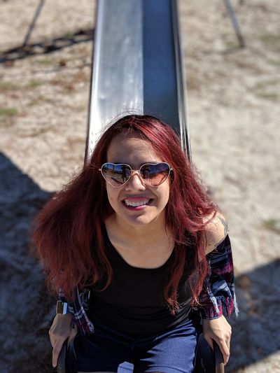 Portrait of smiling young woman sitting on slide at playground