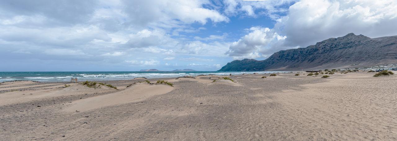 Panoramic shot of playa de famara beach and mountain range on lanzarote