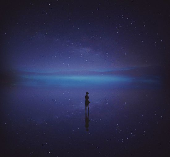 Man standing in sea against sky at night