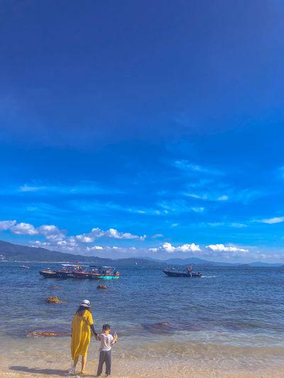 Rear view of women on beach against blue sky