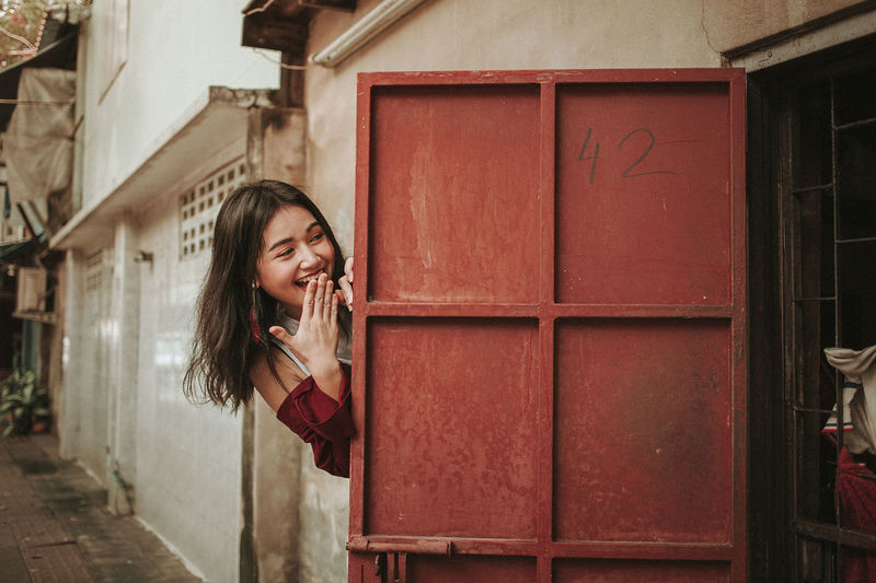Smiling Young Woman Hiding By Door