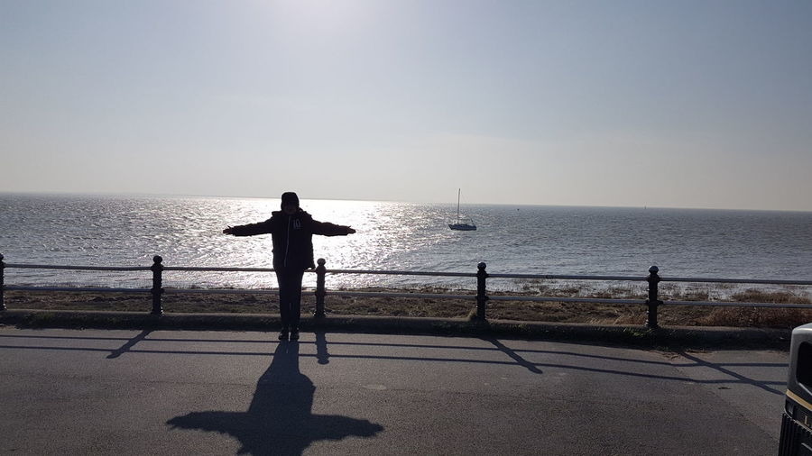 Woman with arms outstretched standing on promenade against sky