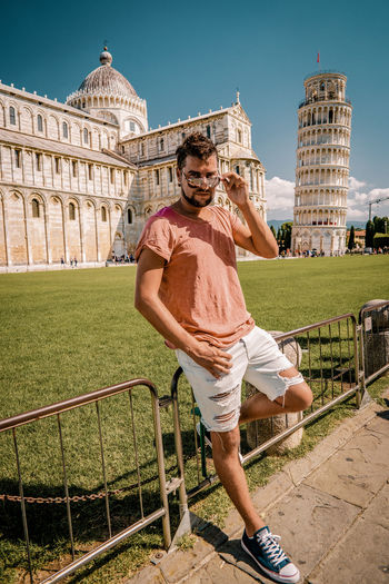 Man Standing Against Leaning Tower Of Pisa