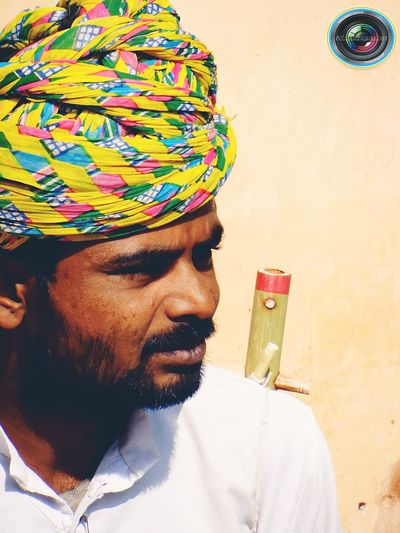 Close-Up Of Male Flautist Wearing Yellow Turban Against Wall