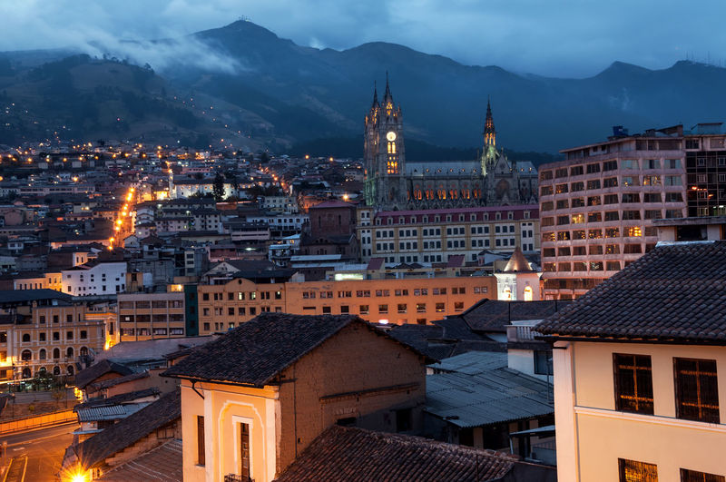 Illuminated city against mountains at twilight