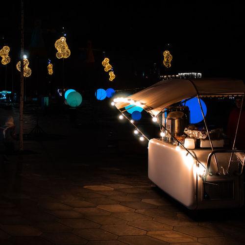 Illuminated carousel in city at night