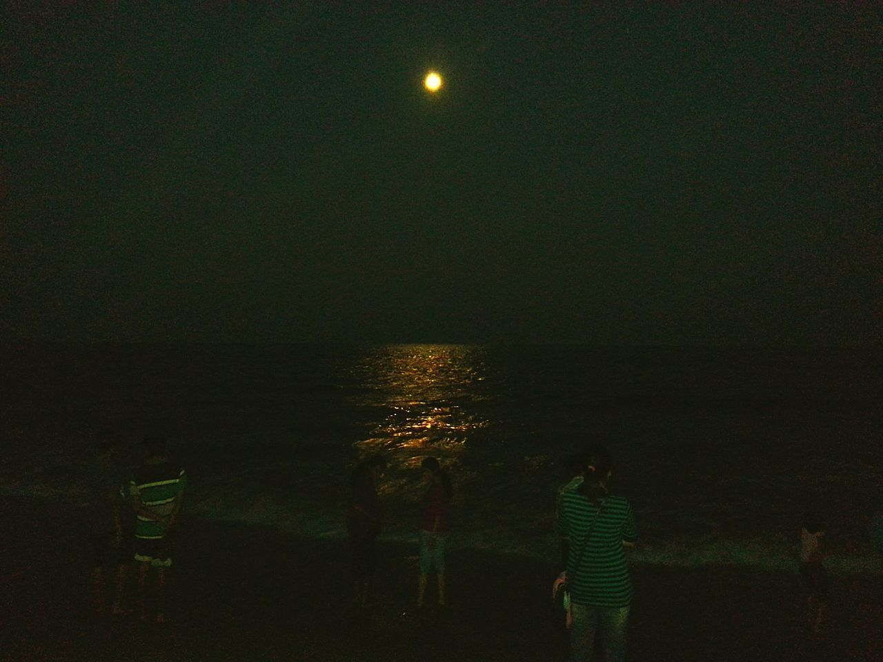 night, rear view, sea, real people, standing, moon, illuminated, outdoors, nature, beach, lifestyles, scenics, water, beauty in nature, sky, one person, horizon over water, astronomy, people