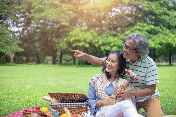 Smiling couple holding flower bouquet while sitting on field by food