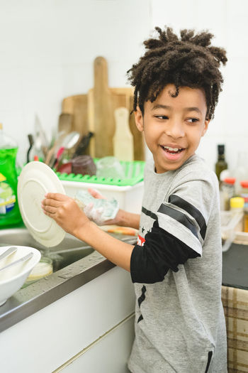 Side view of smiling boy washing dishes in kitchen
