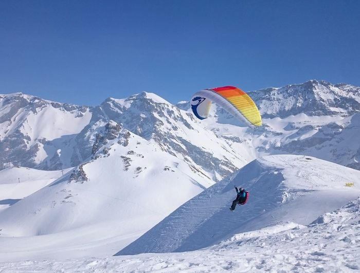 Person paragliding over snowcapped mountain against clear blue sky