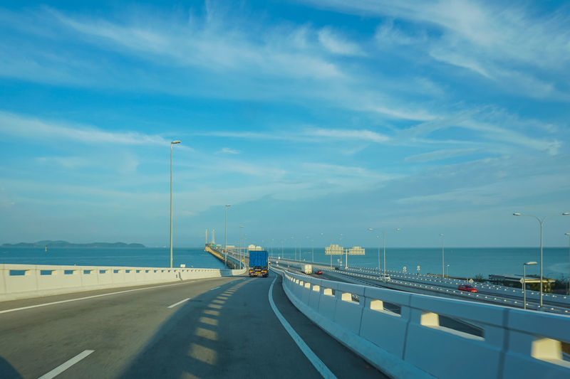 Lorry on the bridge crossing the sea at Penang, Malaysia Transportation Sky Cloud - Sky Road Direction The Way Forward Mode Of Transportation Water Nature Sea Sign Street Highway Land Vehicle Car Symbol Connection Motor Vehicle Street Light No People Bridge - Man Made Structure Outdoors Multiple Lane Highway Crash Barrier