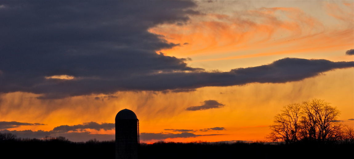 Silhouette Silo On Field Against Orange Cloudy Sky During Sunset