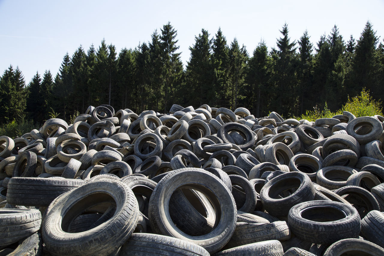 Heap Of Tires Against Trees At Forest