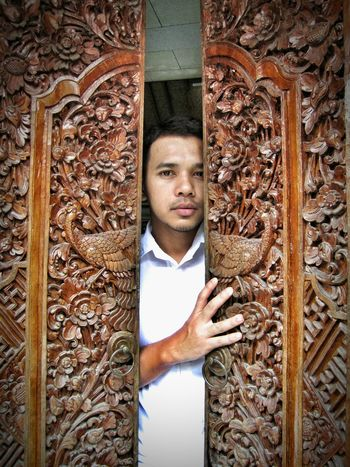 Looking At Camera Portrait Real People Lifestyles Young Adult One Person Standing Outdoors Leisure Activity Day Only Men One Man Only People Adult Adults Only Balinese Bali Crafts Craftsmanship  Magnificent Door Culture Architecture Carvingwood